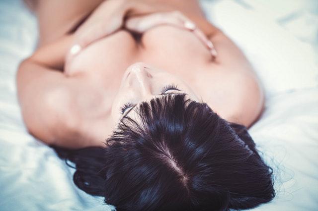 Nahá žena leží v posteli a drží si prsia