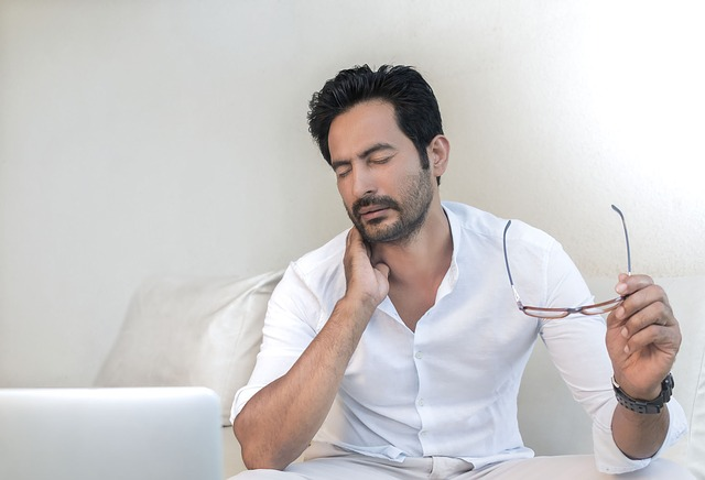 Muž sedí a v ruke drží okuliare, bolesť, únava