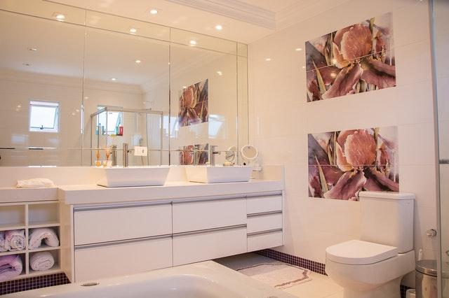 Kúpeľňa v bielych farbách s obrazom na stene a veľkým zrkadlom.jpg