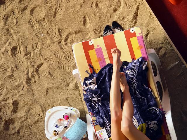Ženské nohy na ležadle položenom na piesku