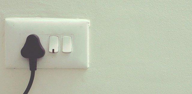 Biela stena s elektrickou zásuvkou a čiernym káblom