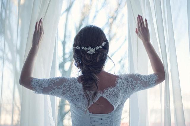 Nevesta v bielych čipkovaných šatách odhŕňa záves na okne.jpg