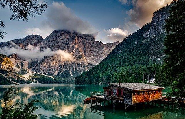 Drevená chata postavená na vode a obrovské modré jazero.jpg