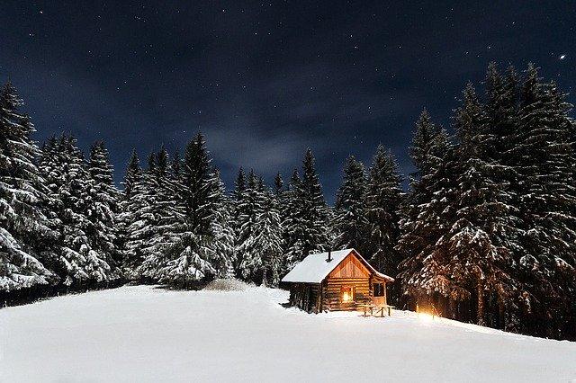 Drevený zrub uprostred zasneženého ihličnatého lesa, so zapáleným svetlom vo vnútri.jpg