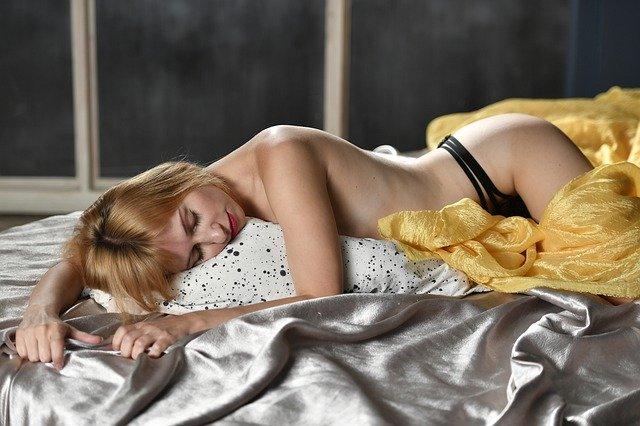 Nahá žena v čiernych nohavičkách leží na posteli na bruchu.jpg