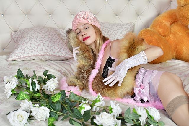 Sexy žena v erotickom prádle s kožušinou okolo krku je na posteli.jpg