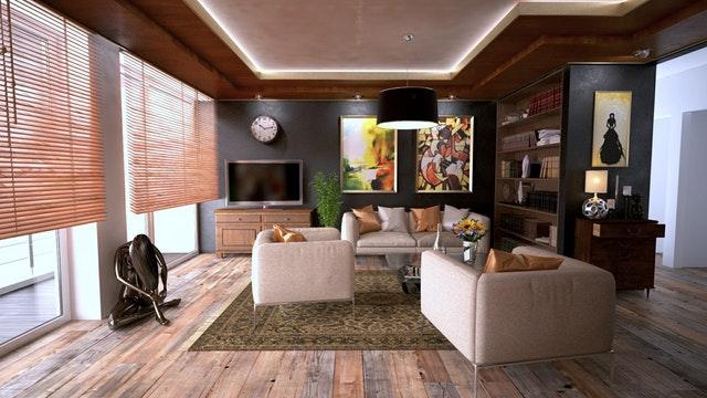 Izba s veľkými oknami, hnedou pohovkou, kovovou sochou a obrazmi na stenách.jpg