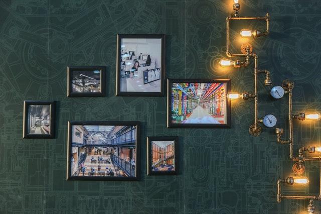 Tmavá stena s obrázkami a lampou vyrobenou z vodovodných trúbok.jpg